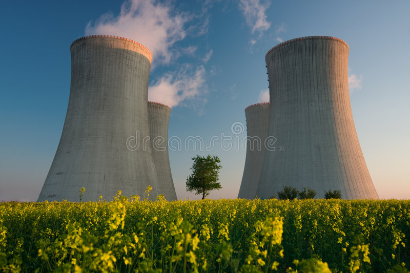 Nuclear power plant. Cooling towers of a nuclear power plant with steam escaping toward the sky. Flowering landscape in the foreground, and a single tree growing stock photography
