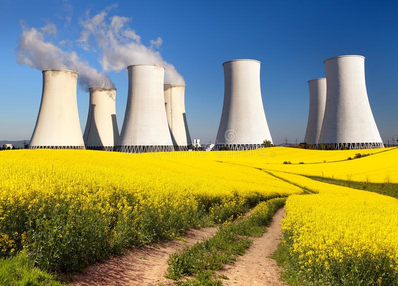Nuclear power plant, cooling tower, field of rapeseed. Panoramic view of Nuclear power plant Jaslovske Bohunice with golden flowering field of rapeseed, canola royalty free stock image
