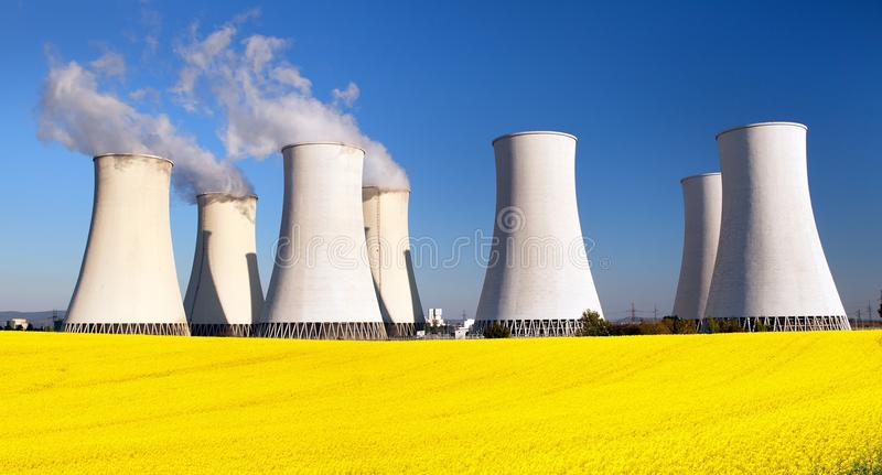 Nuclear power plant, cooling tower, field of rapeseed. Panoramic view of Nuclear power plant Jaslovske, cooling tower, Bohunice with golden flowering field of stock images