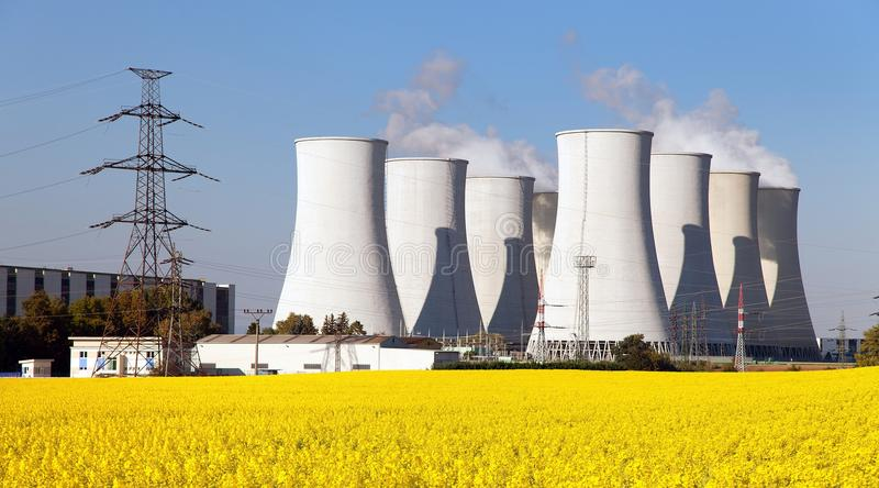 Nuclear power plant, cooling tower, field of rapeseed stock photo