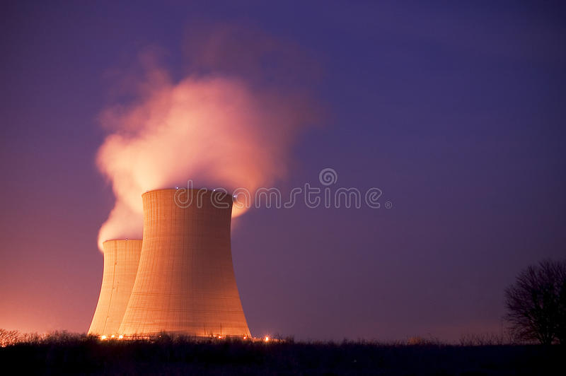 Nuclear Power Plant Cooling Towers at Dusk. Nuclear Power Plant Cooling Towers at with stream pouring out into the purple blue dusk night sky royalty free stock photo