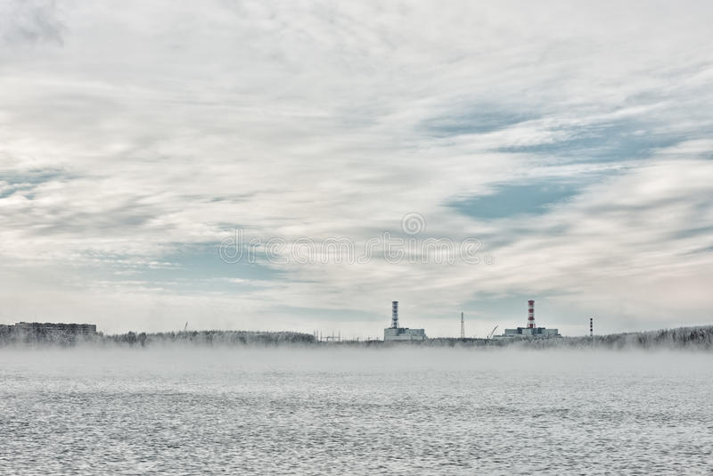 Nuclear power plant on the horizon line in winter. And a nonfreezing technological reservoir stock photography