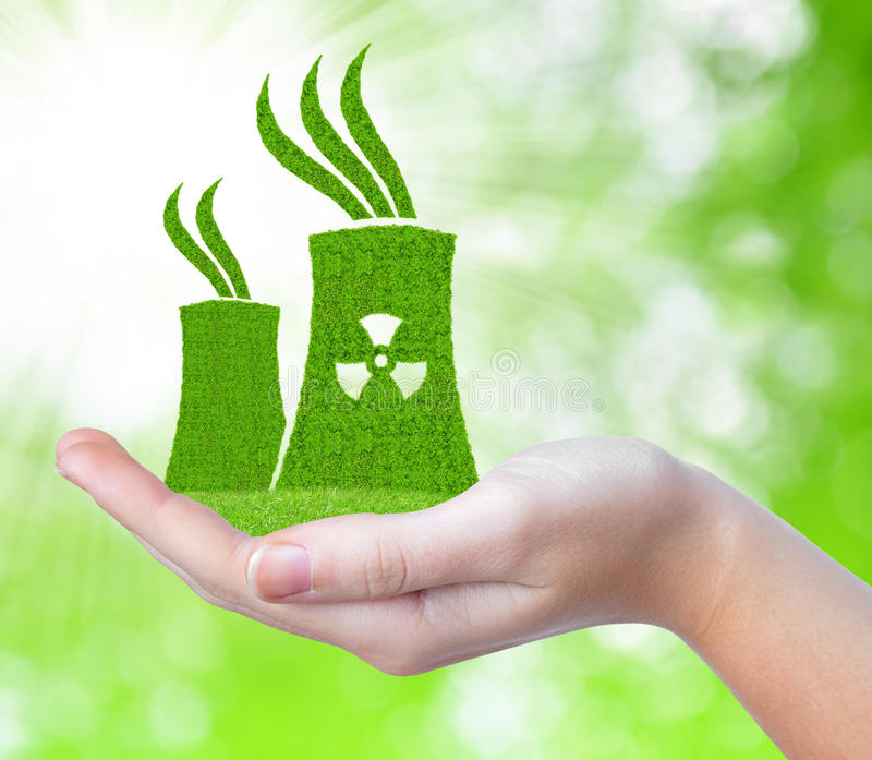 Nuclear power plant icon in hand. On green natural background royalty free stock photo