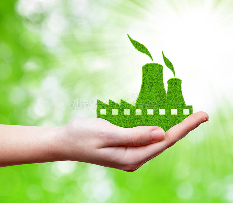 Nuclear power plant icon in hand. On green natural background royalty free stock image