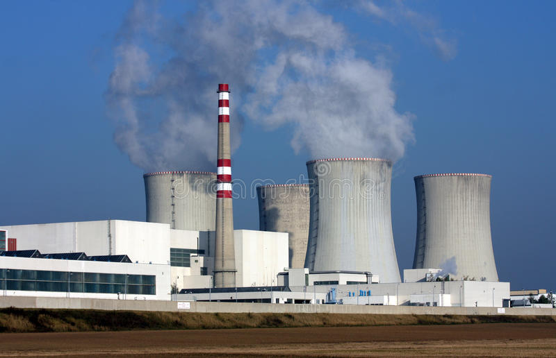 Nuclear power plant over the agriculture field. Nuclear power plant over the brown agriculture field stock photos