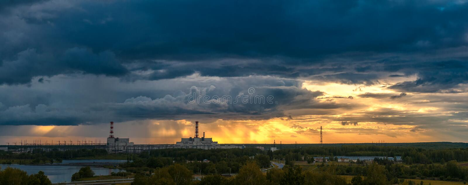 Nuclear power plant at sunset. Panorama of great sunset above power plant summer evening stock image