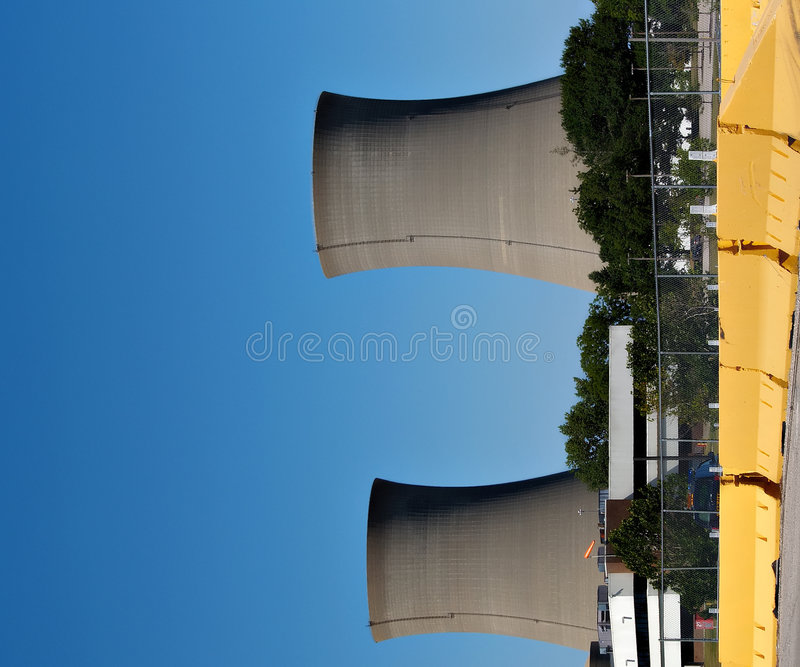 Nuclear Power Stacks. Twin nuclear power stacks rise above an office building into a clear blue sky royalty free stock photo