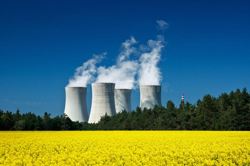 Nuclear power station. In canola field on blue sky royalty free stock photography