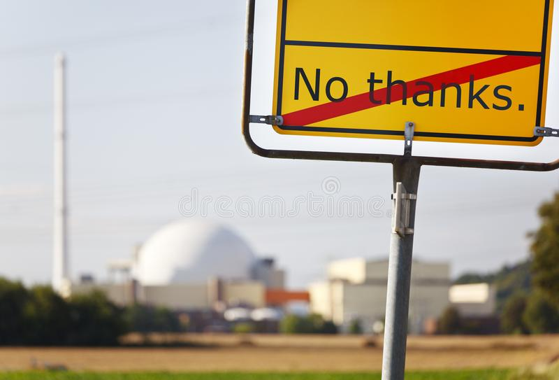 Nuclear Power Station And No Thanks Sign. A yellow sign saying No thanks in front of a nuclear power station royalty free stock images