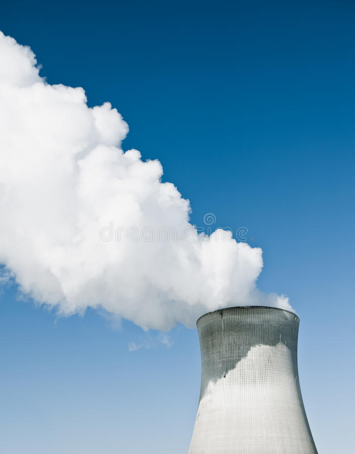 Nuclear Power Station With Steaming Tower. Over clear blue sky royalty free stock photos
