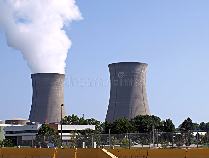 Nuclear Powers Stacks. Twin nuclear power stacks, one of them active with smoke rising into a blue sky stock photo