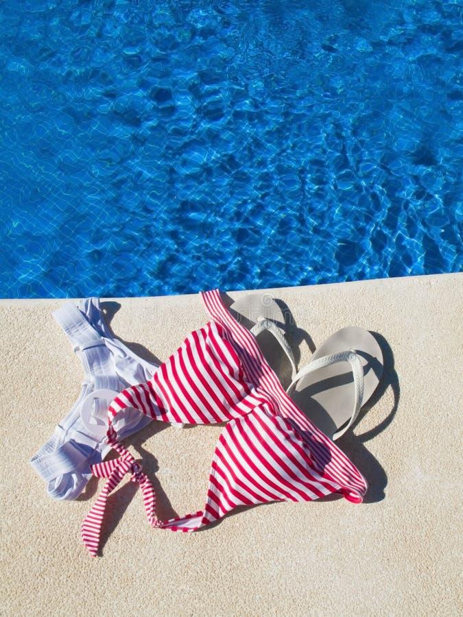 Nude bathing. Femal swimsuit left at pool edge stock photos