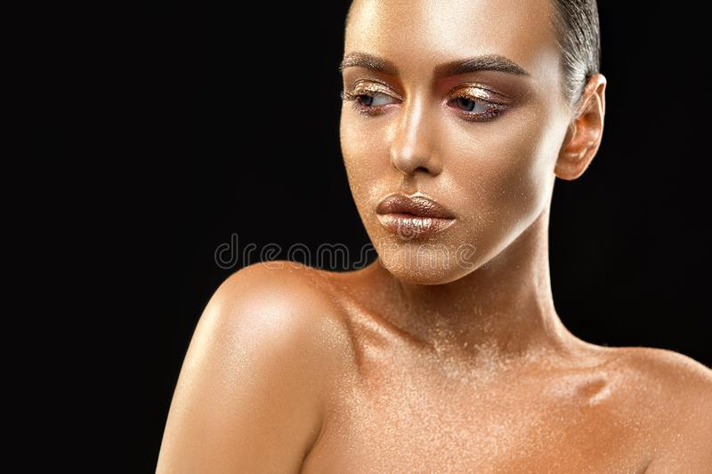 Nude brunette with gold skin artisitc shot. Artistic cropped isolated portrait on black background of a naked brunette with gold skin and fine make up stock photos