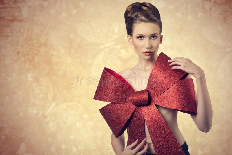 Nude girl with glitter christmas bow royalty free stock photography