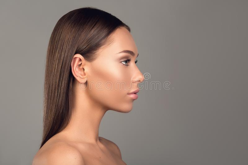 Nude girl with graceful facial features. Side view profile of attractive woman with mild skin and naked body. Her look is tranquil. Copy space in right side royalty free stock image