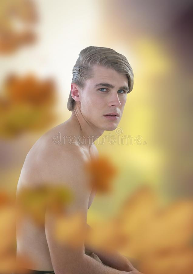 Nude handsome man in forest light opening with leaves. Digital composite of Nude handsome man in forest light opening with leaves stock photo