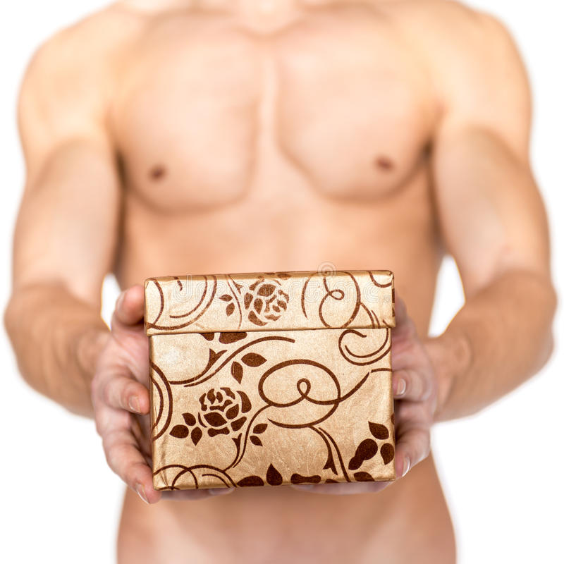 Nude man holding gift box. Gold gift box with floral decoration held by nude man on white background royalty free stock photo
