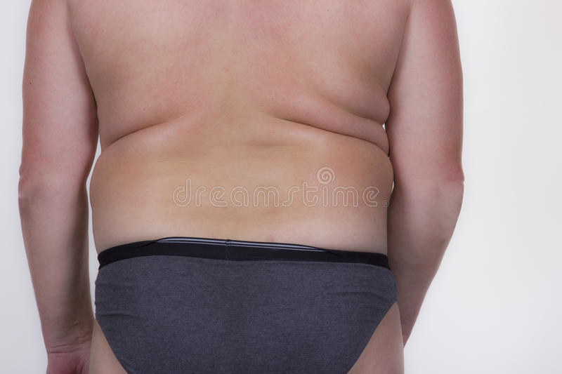 Nude man. Nude fullbody man stands with his back on white background stock photography