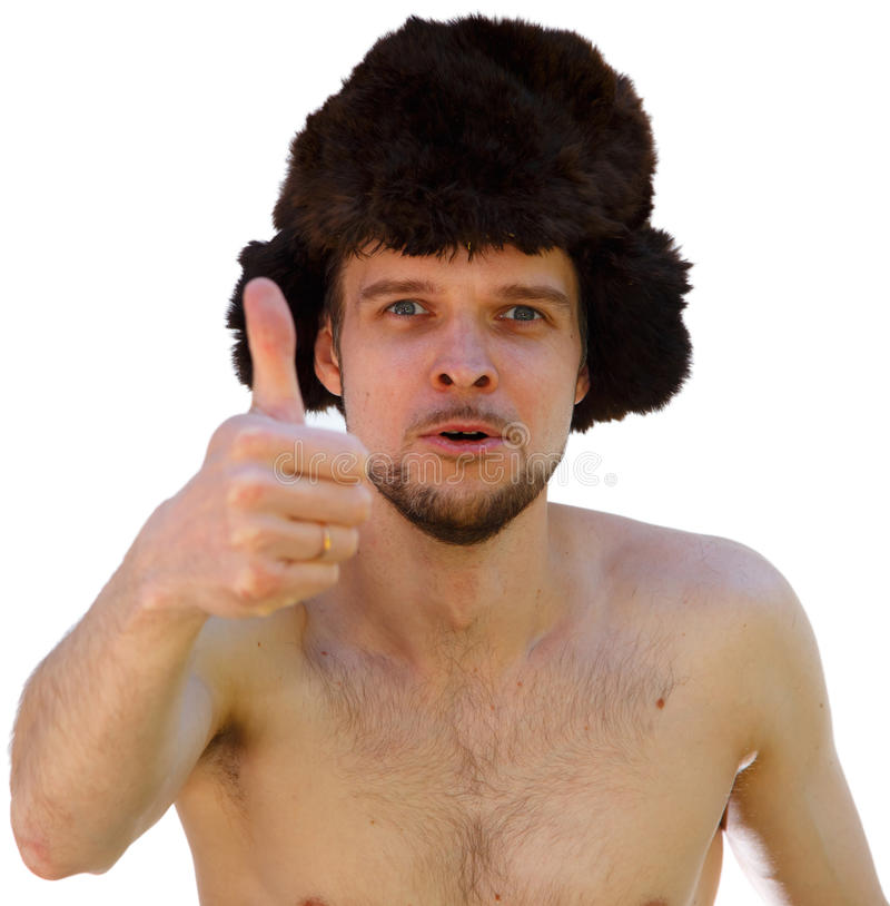 Nude man in fur hat shows thumb. Isolated stock photo