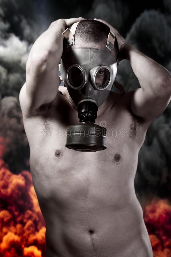 Nude man with gas mask over explosion background. Nude man with gas mask over explosion stock photo