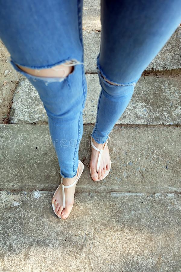 Nude Shoes Woman and Yellow Pineapple Shirt Accessories. Close Up on Girl`s Feet Wearing Nude Sandals and Lack of Blue Jeans on S. Treet Road in The City royalty free stock image