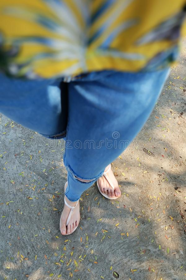Nude Shoes Woman and Yellow Pineapple Shirt Accessories. Close Up on Girl`s Feet Wearing Nude Sandals and Lack of Blue Jeans on S. Treet Road in The City stock images