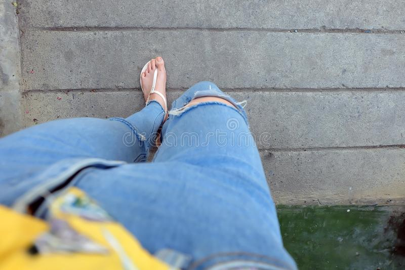 Nude Shoes Woman and Yellow Pineapple Shirt Accessories. Close Up on Girl`s Feet Wearing Nude Sandals and Lack of Blue Jeans on S. Treet Road in The City royalty free stock photos
