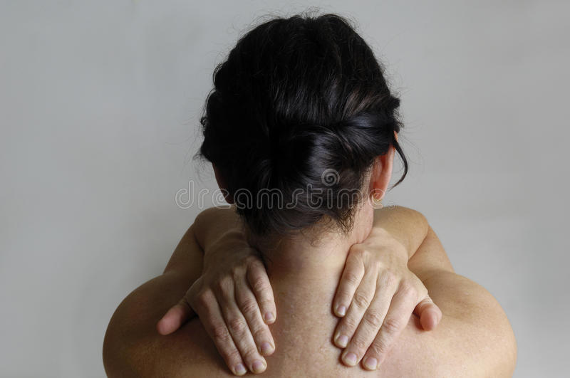 Nude woman with back pain on a gray background stock image