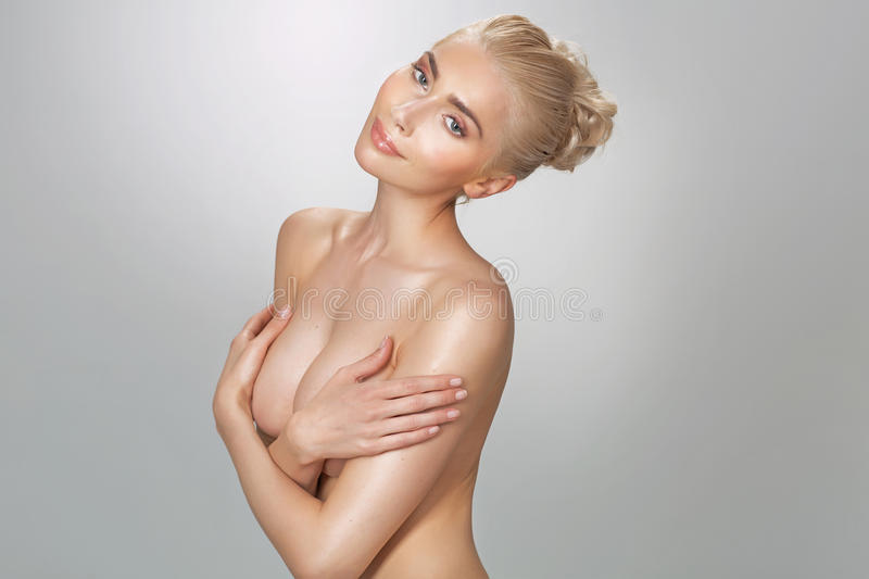 Nude young lady hiding her breasts. Nude young woman hiding her breasts royalty free stock photos