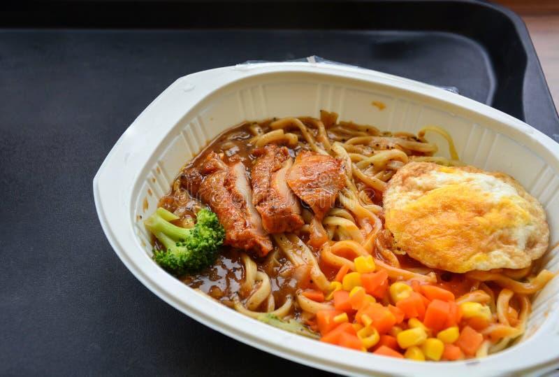 Nudel mit würziger Soße, geschnittenem Huhn, Spiegelei, Brokkoli, Mais und Karotte, sofortige Nahrung, Delikatessen, Tiefkühlkost stockfoto