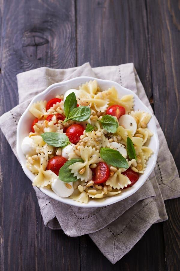 Nudelsalat mit Tomate, Mozzarella, Kiefernnüssen und Basilikum lizenzfreie stockbilder