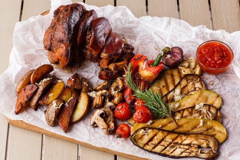 Nudillo asado a la parrilla del cerdo con los tomates asados a la parrilla, los champiñones, el tuétano vagetable, la berenjena,  imagenes de archivo