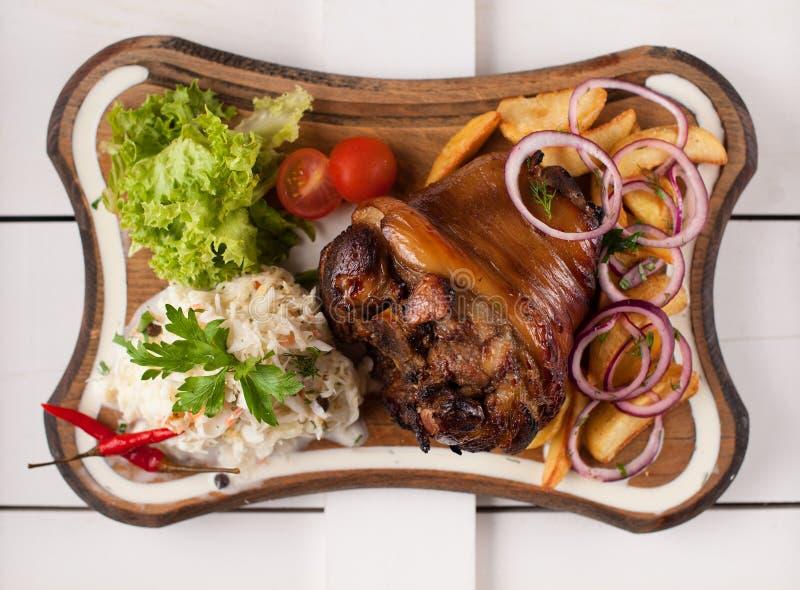 Nudillo cocido del cerdo con la chucrut, las patatas, las cebollas y los verdes en una tabla de cortar de madera Visión desde arr imágenes de archivo libres de regalías