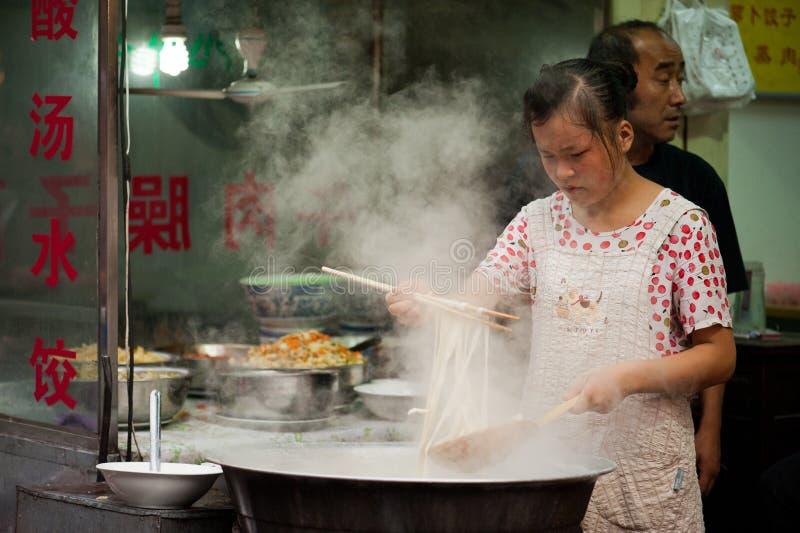 Nudlar för Hui kvinnamatlagning på Muslimgatan i Xian arkivbild