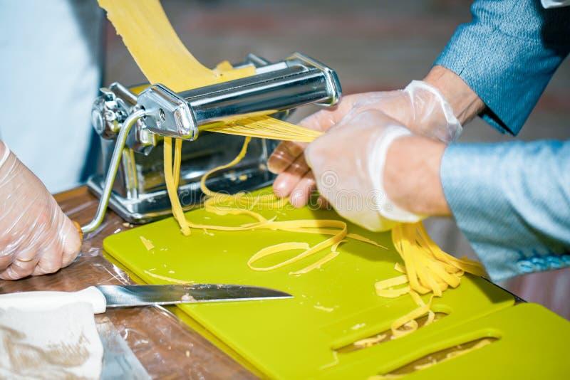 Nudlar för kockdanandespagetti med pastamaskinen på köksbordet royaltyfria foton