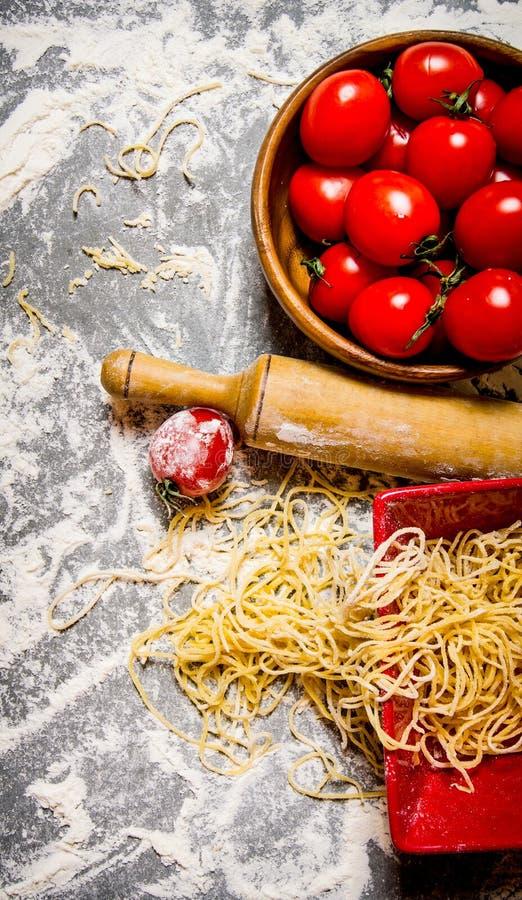 Nudlar med tomater i en kopp och en kavel fotografering för bildbyråer