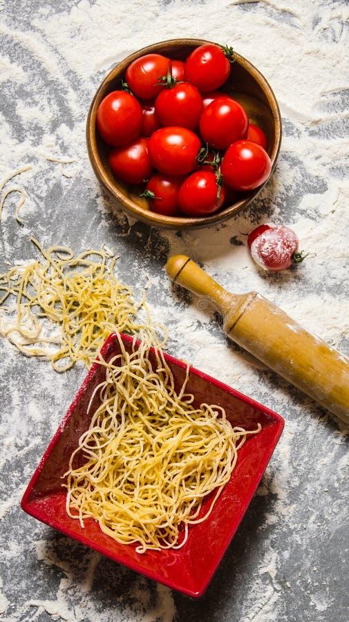Nudlar med tomater och en kavel arkivfoto