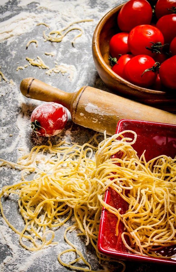 Nudlar med tomater och en kavel fotografering för bildbyråer