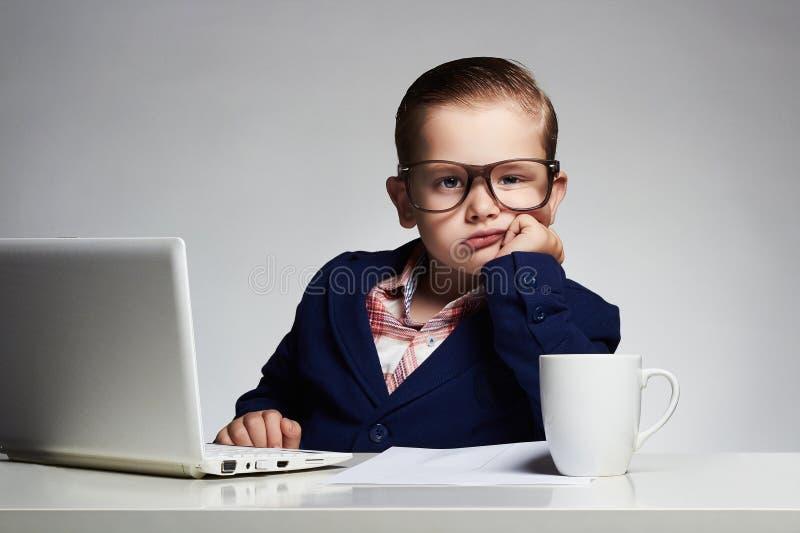 nudna praca Młoda biznesowa chłopiec dziecko w szkłach mały szef w biurze zdjęcia stock