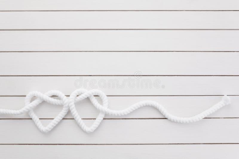 Nudo en forma de corazón en el fondo de madera blanco fotos de archivo libres de regalías
