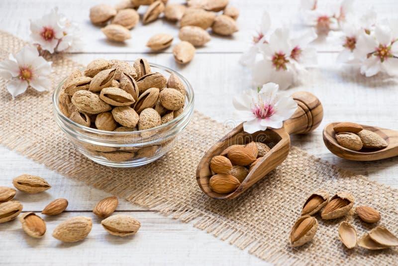 Nueces de la almendra en flores del cuenco y de la almendra en el marco imágenes de archivo libres de regalías
