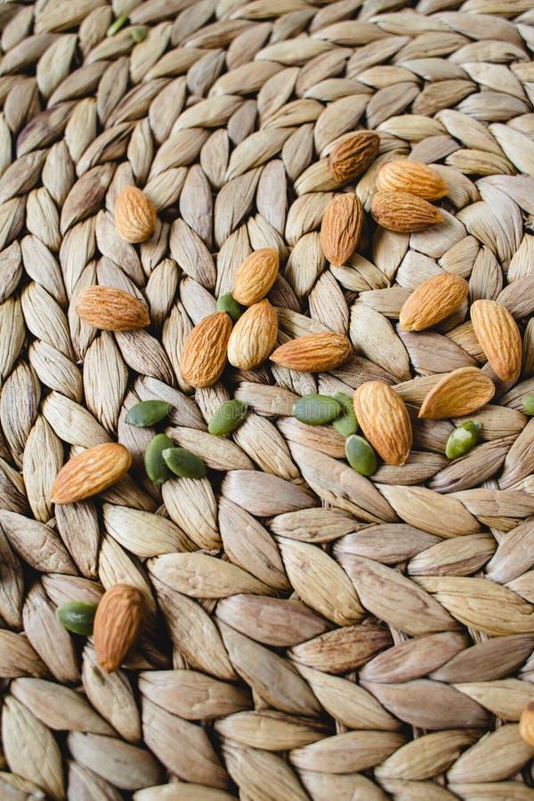 Nueces de las almendras en una servilleta de mimbre natural foto de archivo