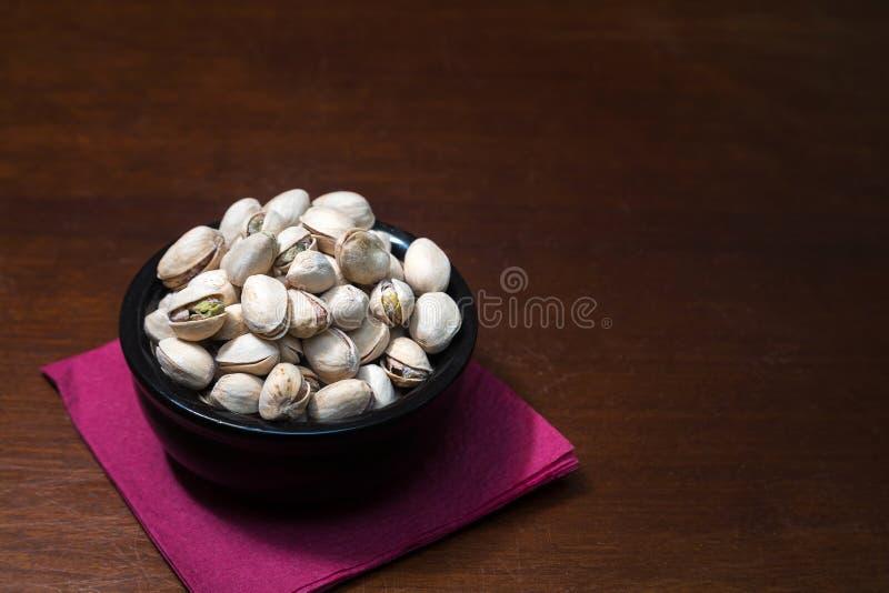 Nueces de pistachos en cuenco de cerámica en la tabla de madera Fondo de la mezcla de la comida, visión superior, espacio de la c imagen de archivo