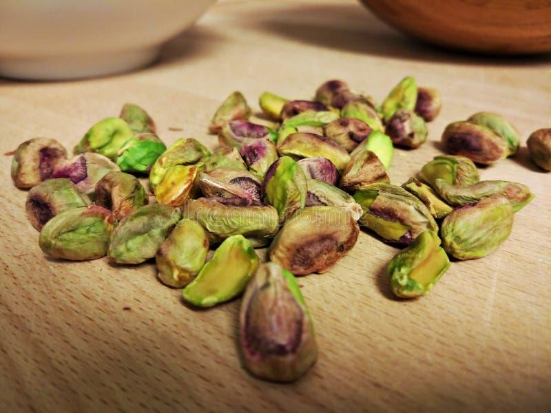 Nueces de pistachos en una tabla de madera y con un cuenco de madera en fondo imagen de archivo