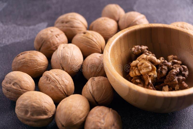 Nueces en cuenco de madera y en superficie azul de la pizarra Nueces y composición sanas de las semillas foto de archivo