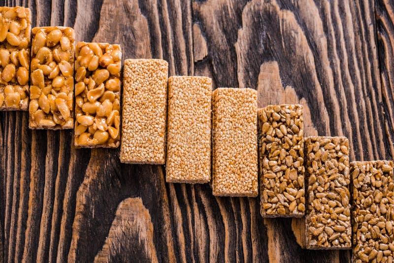 Nueces en el caramelo, miel, nueces del esmalte del azúcar, semillas, semillas de lino en un fondo de madera oscuro de la textura fotografía de archivo