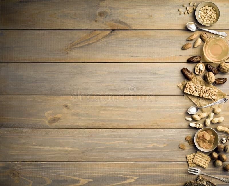 Nueces, frutas secadas, miel y cucharas y bifurcaciones viejas en un fondo de madera de la tabla imágenes de archivo libres de regalías