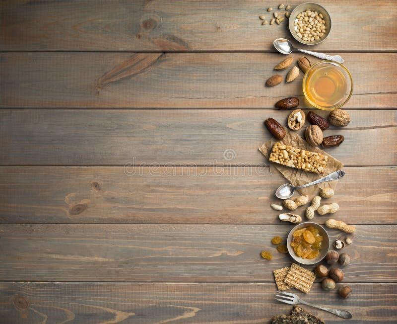 Nueces, frutas secadas, miel y cucharas y bifurcaciones viejas en un viejo fondo de madera de la tabla foto de archivo