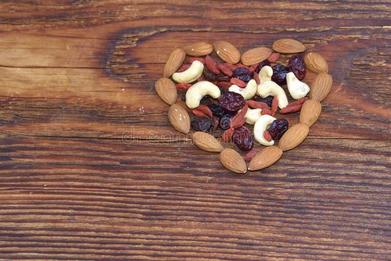 Nueces mezcladas y frutas secadas que forman una corazón-forma en el fondo de madera fotografía de archivo libre de regalías