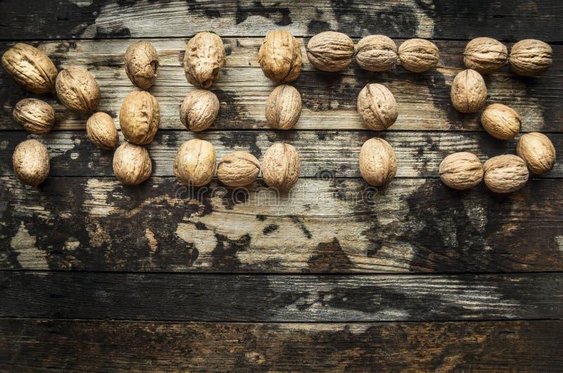 Nueces, presentadas en las nueces de la palabra en fondo rústico de madera, visión superior fotografía de archivo libre de regalías